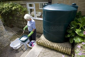 Woman washing clothes with rainwater UK
