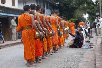 Procession of monks in Luang Prabang in Laos at dawn