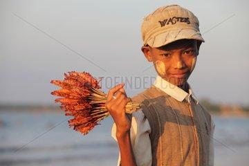 Boy selling Gambas Chaung Tha Beach in Burma