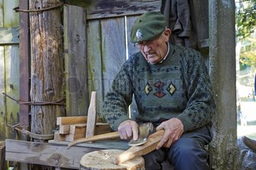 Man working on a piece of wood to do a tool - Basque Country