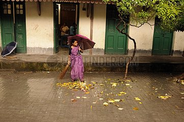 Woman sweeping the course of a school in Calcutta India