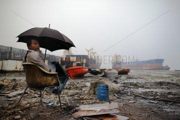Guard monitoring a demolition site in Bangladesh