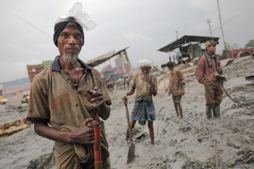 Workers picking up the mud after a rainy night