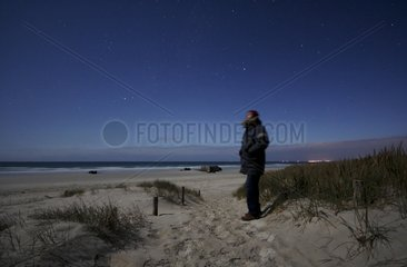 Man on a dune watching the sky lit by the moon France