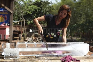 Woman cutting up pieces of ice Cambodia