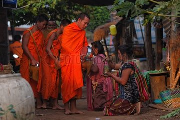 Buddhist monks alms in a village in Laos