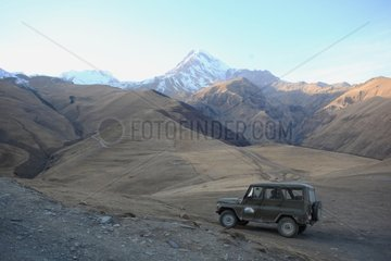 Former military jeep and Mount Kazbek in Georgia on the horizon