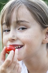 Portrait of girl eating a cherry tomato