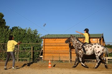 Young woman doing an exercise with his horse France