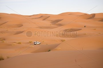 Jeep and camel in the sand dunes of Merzouga Morocco