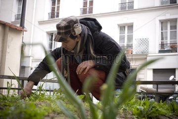 Guerilla Gardening activist in front of a building in Paris