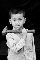 Boy holding a hammer Mondulkiri Cambodia