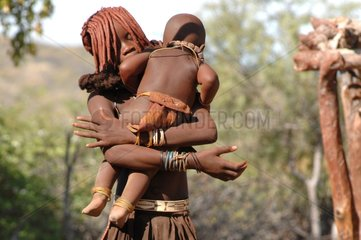 Himba girl holding her brother in his arms Namibia