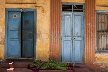 Crippled woman asleep in front of a door not India