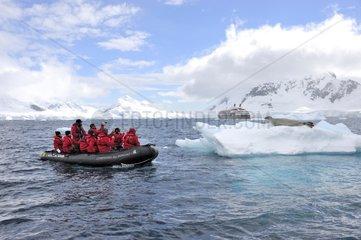 Tourists raft near an iceberg Antarctica