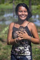 Young girl carrying a young Paca - Amazonas Brazil
