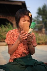 Girl laughing behind his playing card in Burma