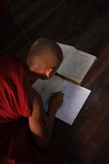 Monk studying Pali on the floor of a monastery in Burma