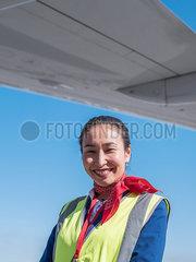 Stewardess steht neben einem Flugzeug p390m2076188
