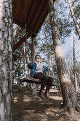 Junge Frau auf einer Schaukel im Wald p1507m2077115