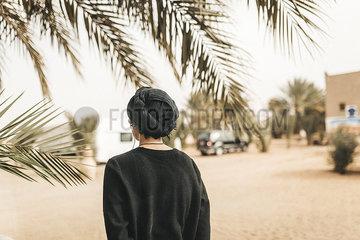 Frau mit Kopftuch in einer Oase unter Palmen p1497m2071421