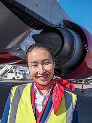 Stewardess steht neben einem Flugzeug p390m2076199