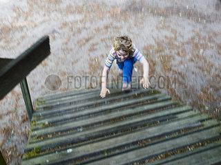 Kleiner Junge rennt Holztreppe hoch p358m2073176