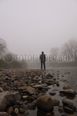 Man standing on stony river bank in fog p597m2076176