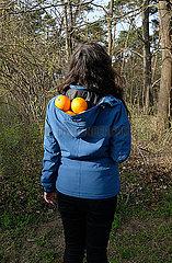 Frau mit Orangen in der Kapuze