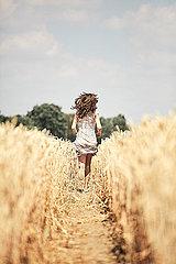 Maedchen rennt durch Kornfeld