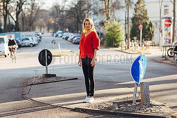 Frau steht nachdenklich auf der Strasse