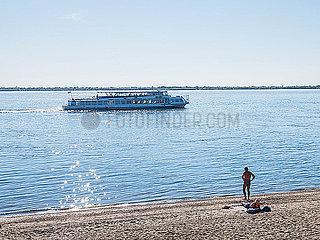 Schiff auf einem Fluss faehrt an Badenden am Strand vorbei