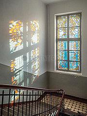 Lichtstrahl faellt durch das Mosaikfensterglas in einem alten Treppenhaus