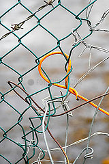 A wire mesh fence repaired with random pieces of other wire