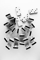 Black and white plastic dominoes standing on end and crowded together on a white surface  with four lying down
