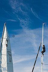 Segelyacht mit einem Mann hoch im Mast