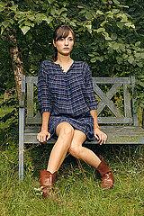 Junge Frau auf einer Gartenbank