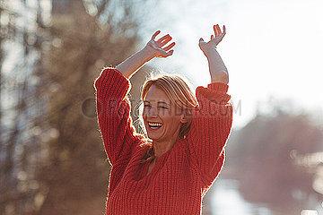 Frau streckt gluecklich die Arme aus
