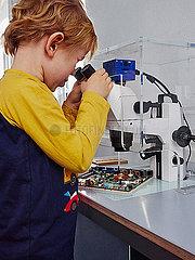 Junge schaut durch ein Mikroskop