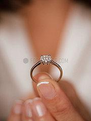 Frau haelt Diamantring in der Hand