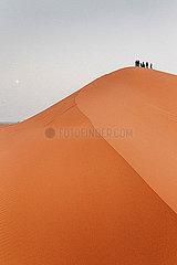 Menschen auf Duenen in der Wueste Sahara in Marokko