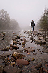 Man standing on stony river bank in fog
