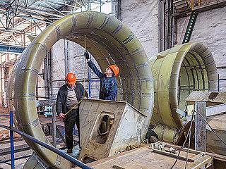 Fabrikarbeiter arbeiten an den Turbinen eines Luftkissenbootes in einer Schiffsfabrik