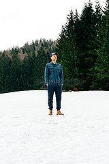 Mann steht entspannt im Schnee