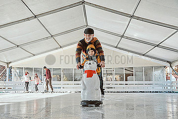Grandfather and grandson on the ice rink  ice skating  using ice bear figure as prop