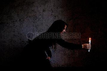 Frau haelt eine Kerze
