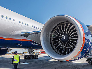 Flugzeugkapitaen macht einen Rundgang um Flugzeug Boeing 777 - 300 und Triebwerk
