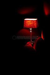 Beleuchtete Nachtischlampe am Bett
