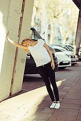 Frau lehnt erschoepft an Wand
