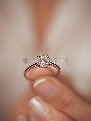 Frau haelt Diamantring in der Hand p1522m2071764